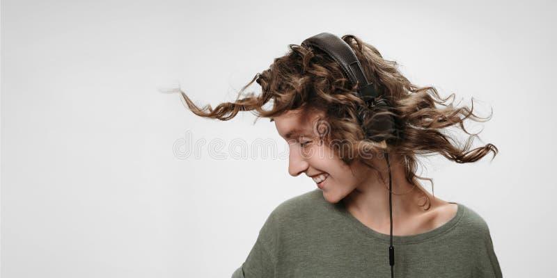 Η ξένοιαστη εύθυμη νέα σγουρή γυναίκα ακούει αγαπημένη μουσική στοκ εικόνες
