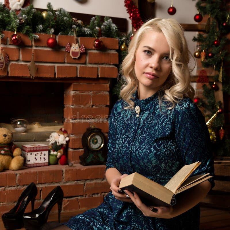 Η ξανθή γυναίκα διαβάζει ένα βιβλίο κοντά στην εστία με τις διακοσμήσεις Χριστουγέννων στοκ εικόνες