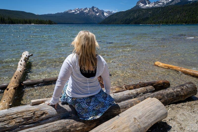 Η ξανθή γυναίκα με την πλάτη που αντιμετωπίζει τη κάμερα κοιτάζει έξω στα πριονωτά βουνά καθμένος στα κούτσουρα στη λίμνη σολομών στοκ εικόνες με δικαίωμα ελεύθερης χρήσης