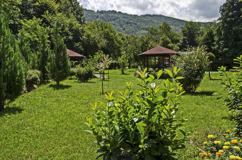 Η ξύλινη αλκόβα με τον πάγκο, πίνακας με την παιδική χαρά των παιδιών στη θέση μοναστηριών για χαλαρώνει, βουνό βαλκανικό, κοντά  στοκ φωτογραφία με δικαίωμα ελεύθερης χρήσης