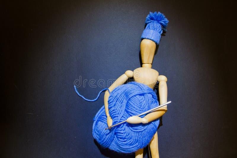 Η ξύλινη κούκλα μαριονετών κρατά μια σφαίρα του μπλε γάντζου νημάτων και τσιγγελακιών στα χέρια της, και φορά ένα πλεκτό χειμεριν στοκ εικόνες με δικαίωμα ελεύθερης χρήσης