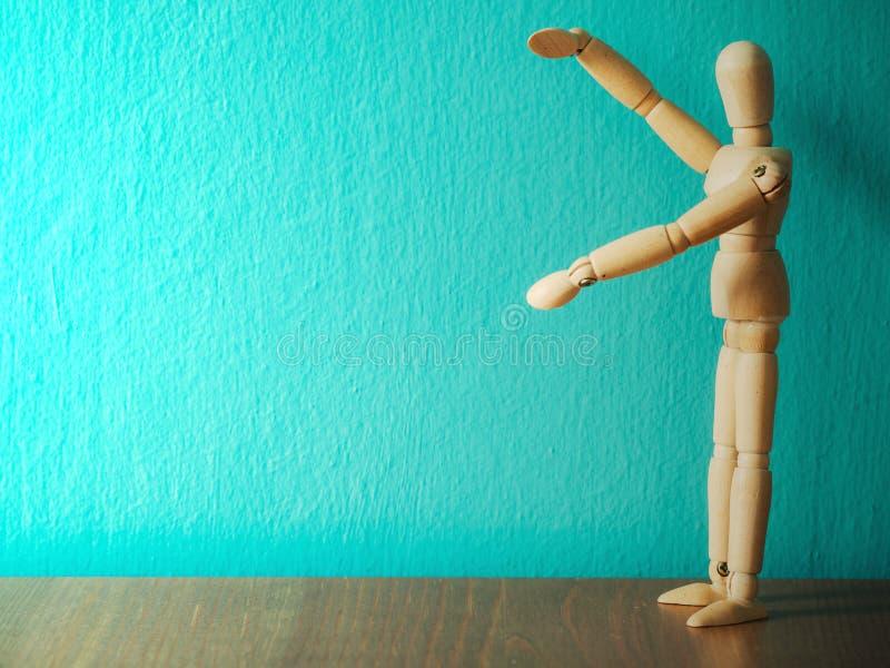 Η ξύλινη μαριονέτα παρουσιάζει χέρια κρατώντας το κενό σημάδι Ξύλινη στάση μαριονετών στον ξύλινο πίνακα το υπόβαθρο είναι τυρκου στοκ φωτογραφία με δικαίωμα ελεύθερης χρήσης