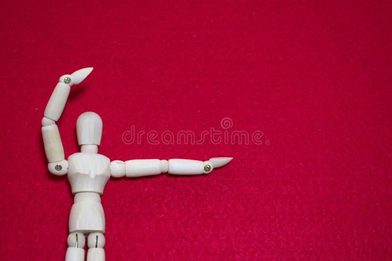Η ξύλινη μαριονέτα σε ακρυλικό κόκκινου χρώματος αισθητό κρατά ψηλά την πράξη βραχιόνων όπως παρόντα κάτι στοκ εικόνα με δικαίωμα ελεύθερης χρήσης