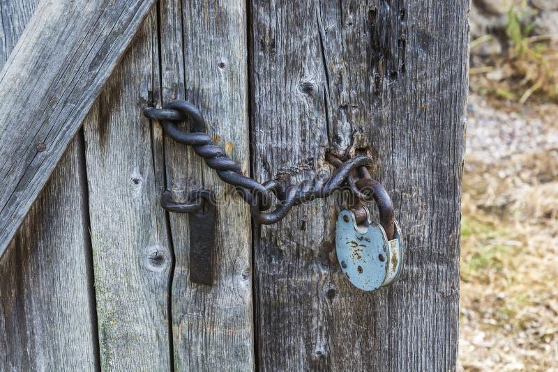Η ξύλινη πόρτα είναι κλειστή στο παλαιό λουκέτο στοκ φωτογραφία με δικαίωμα ελεύθερης χρήσης