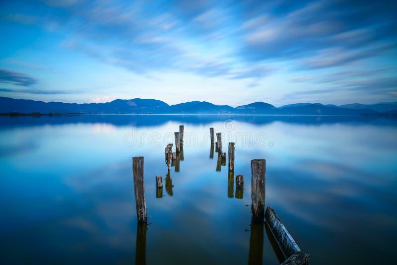 Η ξύλινος αποβάθρα ή ο λιμενοβραχίονας παραμένει σε ένα μπλε ηλιοβασίλεμα λιμνών και μια αντανάκλαση ουρανού στο νερό. Versilia Το στοκ φωτογραφία με δικαίωμα ελεύθερης χρήσης