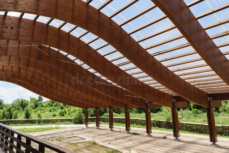 Η ογκώδης ξύλινη δομή στεγών ακτίνων με το S έκαμψε διαμορφωμένος και που κάλυψε με το διαφανές φύλλο πολυανθράκων στοκ εικόνα