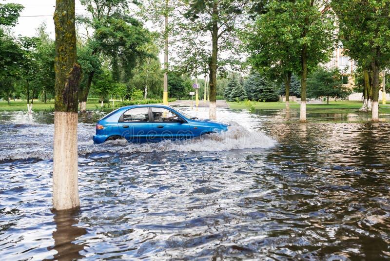 Η οδήγηση αυτοκινήτων σε έναν πλημμυρισμένο δρόμο κατά τη διάρκεια μιας πλημμύρας που προκαλείται από τη δυνατή βροχή στοκ εικόνες με δικαίωμα ελεύθερης χρήσης