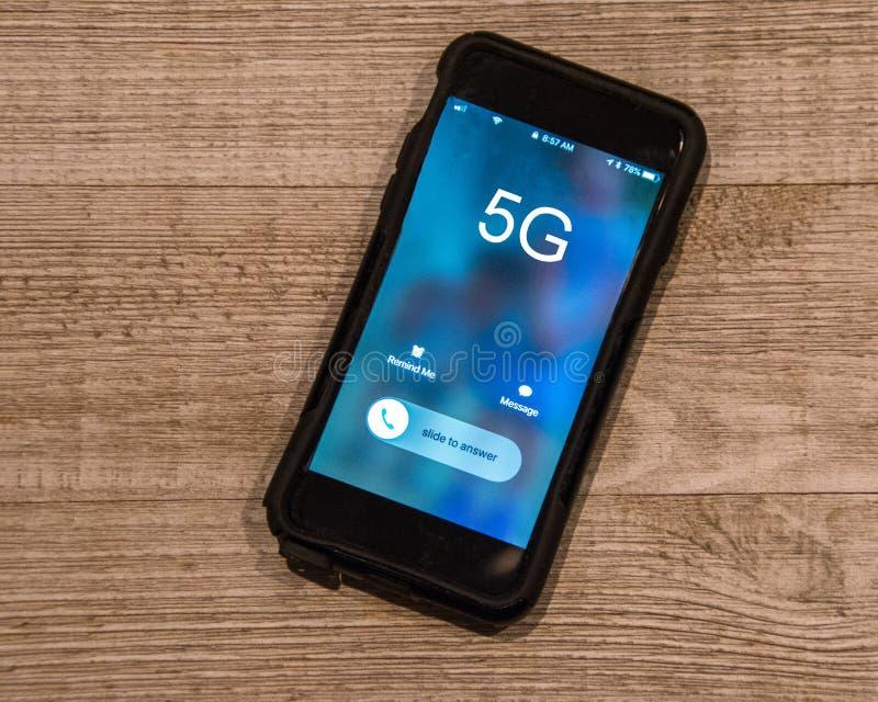Κινητό τηλέφωνο στο ξύλινο υπόβαθρο Η οθόνη λέει 5G στοκ εικόνες