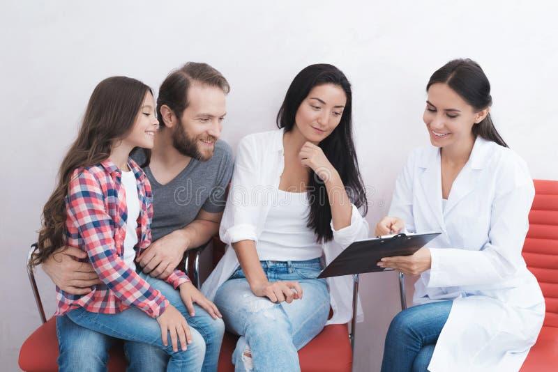 Η οικογένεια ήρθε να δει έναν οδοντίατρο σε μια ιατρική κλινική Οι βοήθειες γραμματέων συμπληρώνουν όλα τα απαραίτητα έγγραφα στοκ φωτογραφία