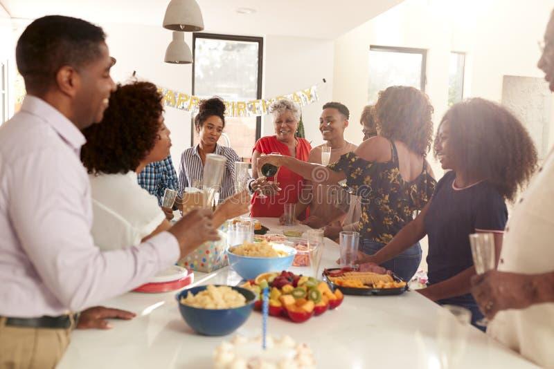 Η οικογένεια αφροαμερικάνων τριών γενεάς που αυξάνει τα γυαλιά για να κάνει μια φρυγανιά κατά τη διάρκεια ενός εορτασμού στο σπίτ στοκ φωτογραφία