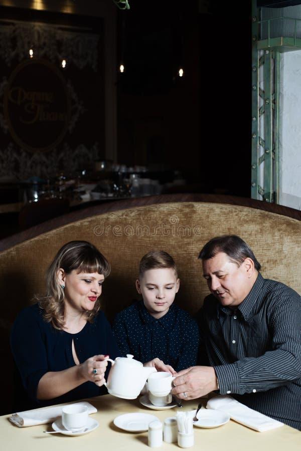 Η οικογένεια ενώθηκε σε έναν καφέ Το Mom, μπαμπάς, γιος πίνει το τσάι Είναι ευτυχείς από κοινού Ευτυχής έννοια οικογενειακού μεση στοκ φωτογραφία