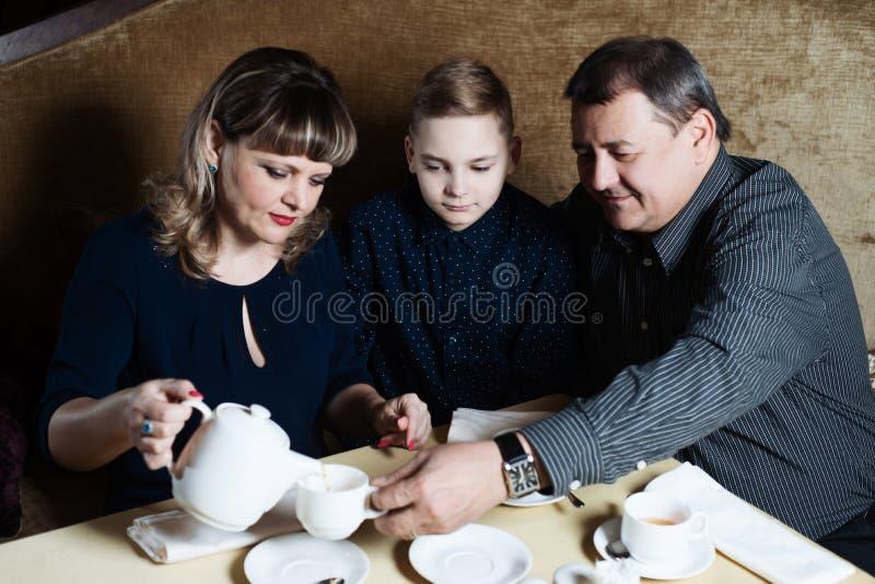 Η οικογένεια ενώθηκε σε έναν καφέ Το Mom, μπαμπάς, γιος πίνει το τσάι Είναι ευτυχείς από κοινού Ευτυχής έννοια οικογενειακού μεση στοκ φωτογραφίες με δικαίωμα ελεύθερης χρήσης
