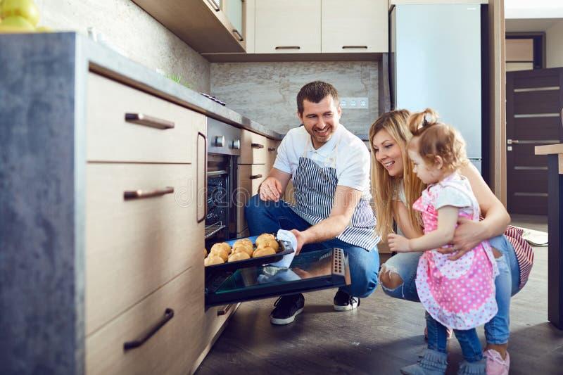 Η οικογένεια θα πάρει έναν δίσκο με τα μπισκότα από το φούρνο στοκ φωτογραφίες με δικαίωμα ελεύθερης χρήσης