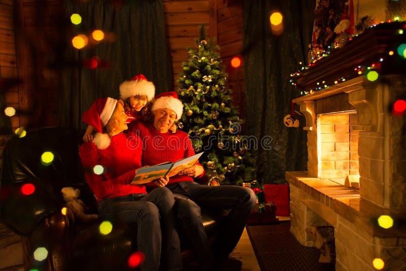 Η οικογένεια διάβασε τη συνεδρίαση βιβλίων Χριστουγέννων στο λεωφορείο μπροστά από την εστία στο εορταστικό διακοσμημένο εσωτερικ στοκ εικόνες