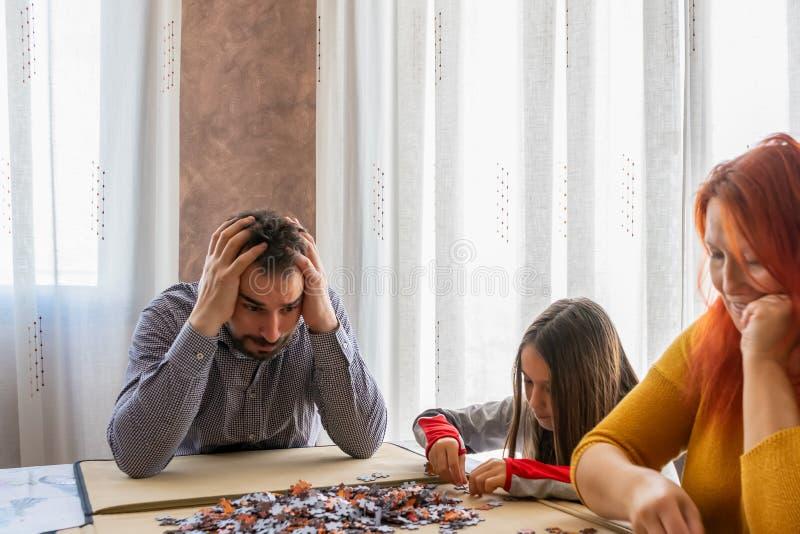 Η οικογένεια κάνει παζλ στο σαλόνι στο σπίτι στοκ εικόνα