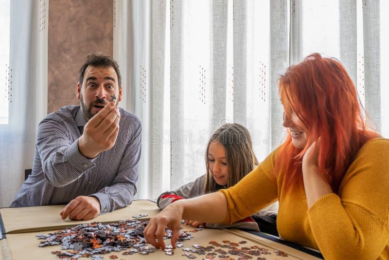 Η οικογένεια κάνει παζλ στο σαλόνι στο σπίτι στοκ εικόνες