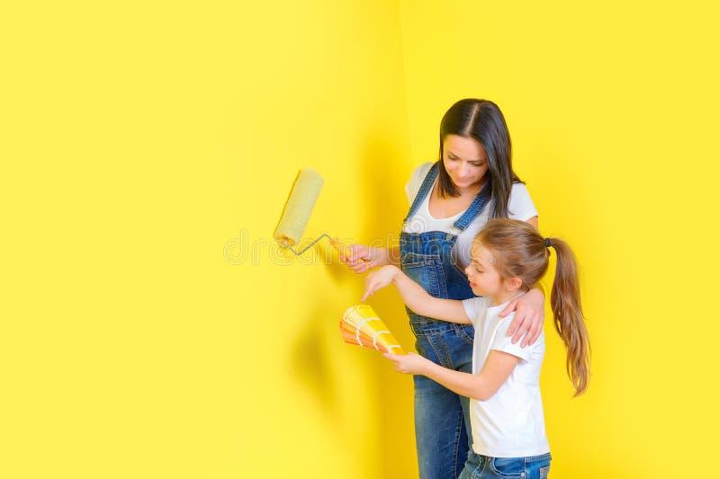 Η οικογένεια κάνει τις επισκευές στο σπίτι, χρωματίζοντας τους τοίχους στοκ φωτογραφία