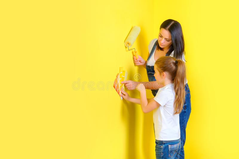 Η οικογένεια κάνει τις επισκευές στο σπίτι, χρωματίζοντας τους τοίχους στοκ εικόνες