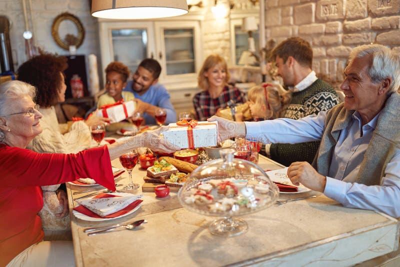Η οικογένεια και οι φίλοι απολαμβάνουν στα δώρα γευμάτων και ανταλλαγής Χριστουγέννων από κοινού στοκ φωτογραφία
