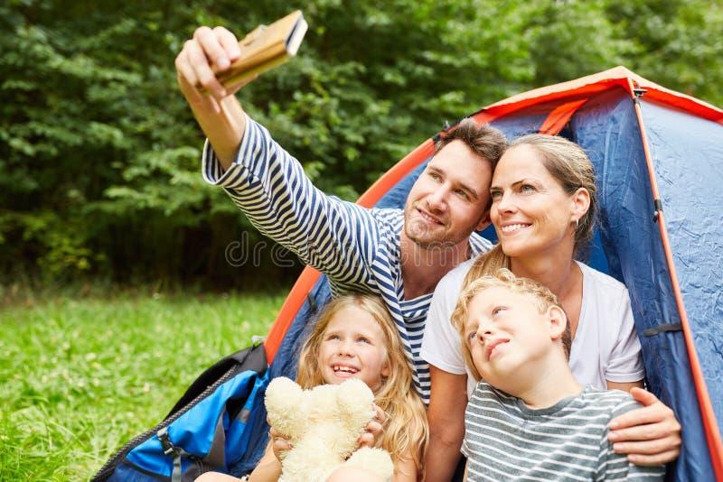 Η οικογένεια με τα παιδιά που στρατοπεδεύουν κάνει selfie στοκ φωτογραφίες