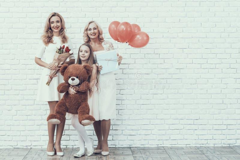 Η οικογένεια με το κορίτσι στο άσπρο παιχνίδι εκμετάλλευσης φορεμάτων αντέχει στοκ φωτογραφίες