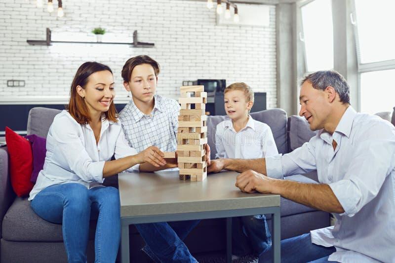 Η οικογένεια παίζει τα επιτραπέζια παιχνίδια μέσα στο δωμάτιο στοκ εικόνες