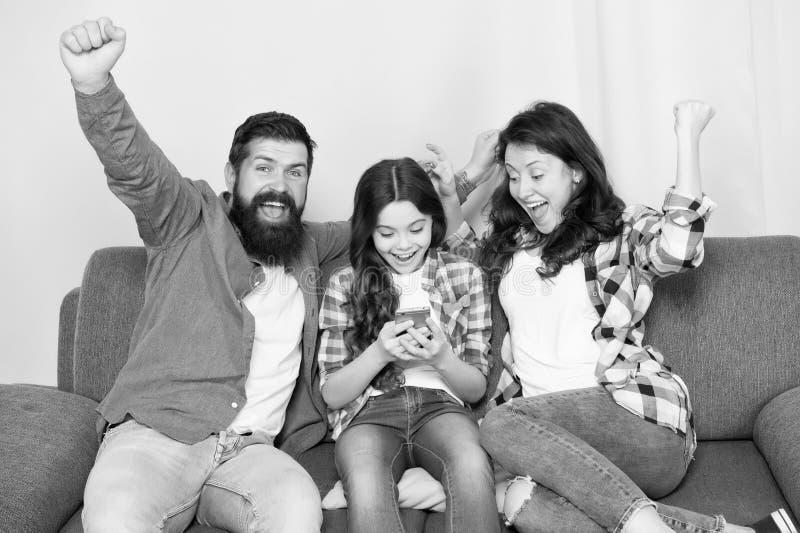 Η οικογένεια περνά το Σαββατοκύριακο από κοινού Smartphone χρήσης μικρών κοριτσιών παιδιών με τους γονείς Φιλική οικογένεια που έ στοκ εικόνες