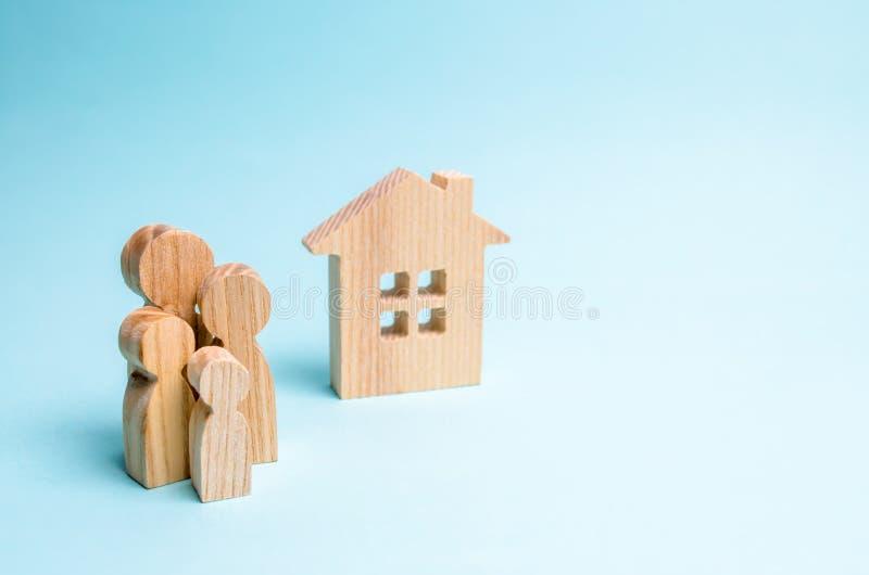 Η οικογένεια στέκεται κοντά σε ένα ξύλινο σπίτι σε ένα μπλε υπόβαθρο Η έννοια της προσιτών κατοικίας και των υποθηκών για την αγο στοκ εικόνα