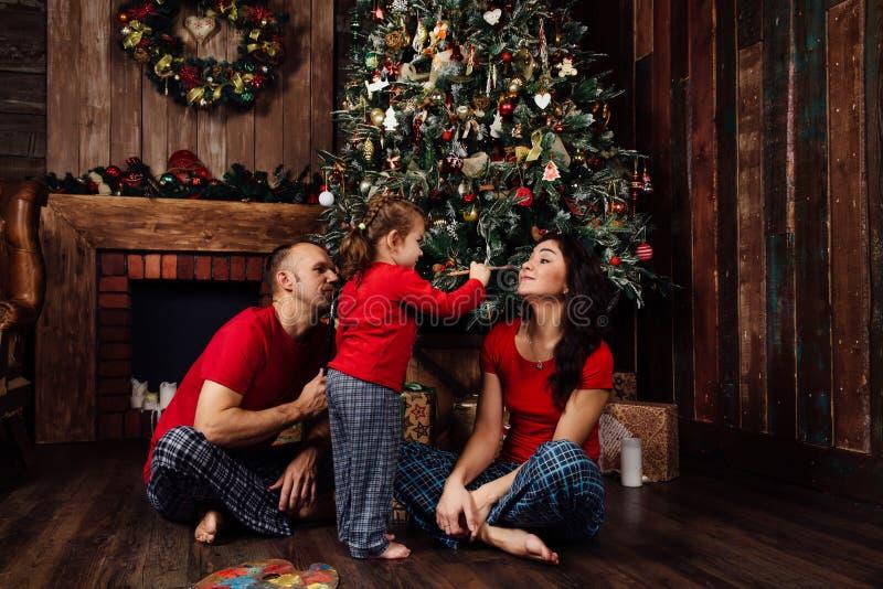 Η οικογένεια στα παιχνίδια πυτζαμών δίπλα σε ένα χριστουγεννιάτικο δέντρο και μια εστία στοκ εικόνα