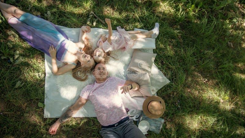 Η οικογένεια στηρίζεται στο πάρκο - πατέρας, μητέρα και κόρη έχει το πρόγευμα - τοπ άποψη στοκ εικόνες