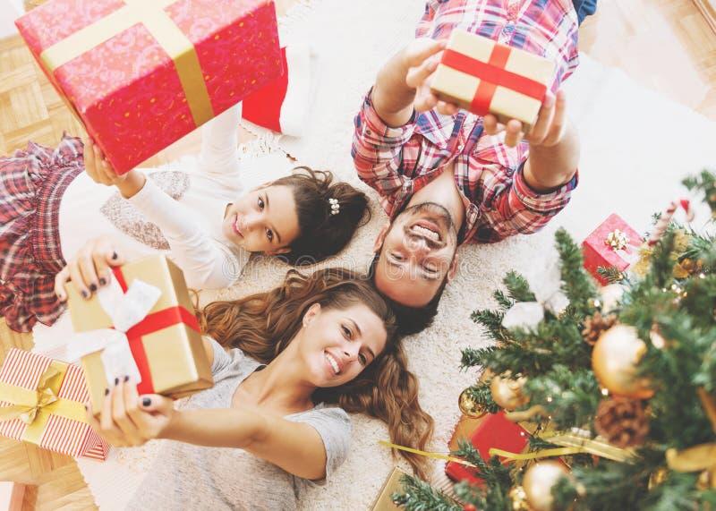 Η οικογένεια συλλέγει γύρω από ένα χριστουγεννιάτικο δέντρο, το κράτημα παρουσιάζει στοκ εικόνα με δικαίωμα ελεύθερης χρήσης