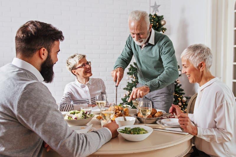 Η οικογένεια σύλλεξε πέρα από τις διακοπές Χριστουγέννων, γιορτάζοντας, έχοντας το μεσημεριανό γεύμα στοκ εικόνες με δικαίωμα ελεύθερης χρήσης