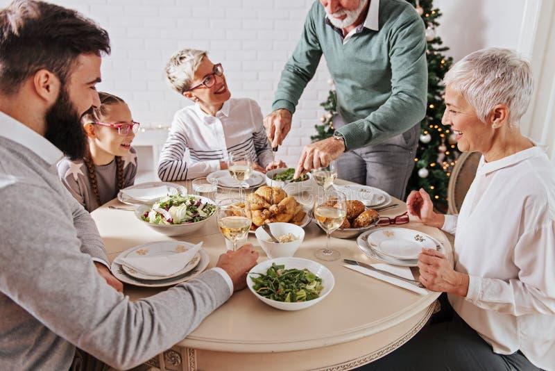 Η οικογένεια σύλλεξε πέρα από τις διακοπές Χριστουγέννων, γιορτάζοντας, έχοντας το μεσημεριανό γεύμα στοκ εικόνα με δικαίωμα ελεύθερης χρήσης