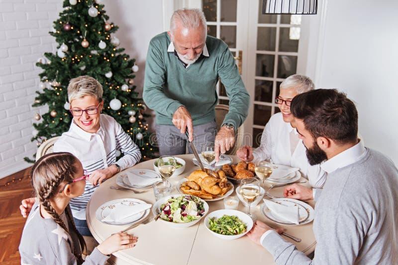 Η οικογένεια σύλλεξε πέρα από τις διακοπές Χριστουγέννων, γιορτάζοντας, έχοντας το μεσημεριανό γεύμα στοκ φωτογραφίες με δικαίωμα ελεύθερης χρήσης