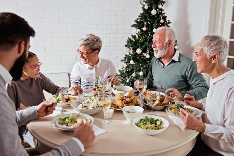 Η οικογένεια σύλλεξε πέρα από τις διακοπές Χριστουγέννων, γιορτάζοντας, έχοντας το μεσημεριανό γεύμα στοκ φωτογραφία