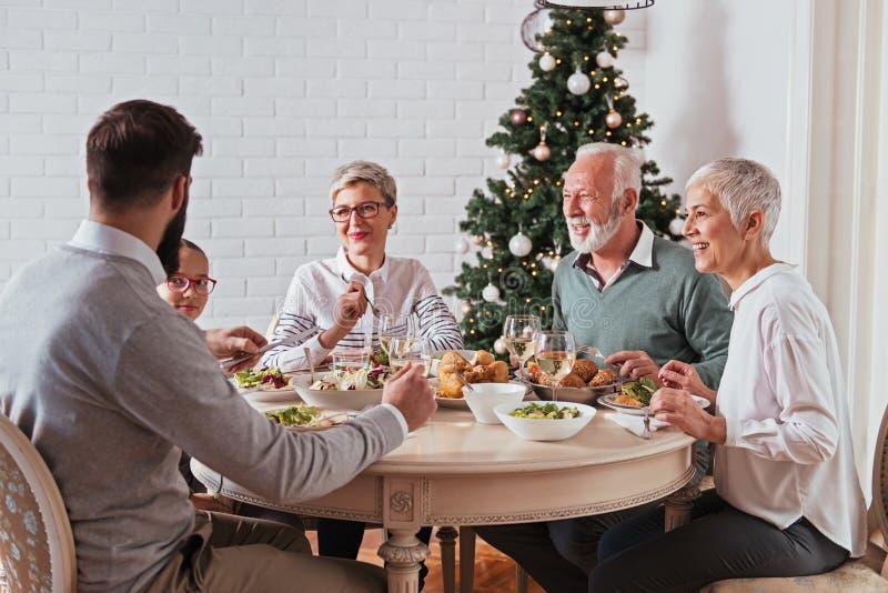 Η οικογένεια σύλλεξε πέρα από τις διακοπές Χριστουγέννων, γιορτάζοντας, έχοντας το μεσημεριανό γεύμα στοκ εικόνες