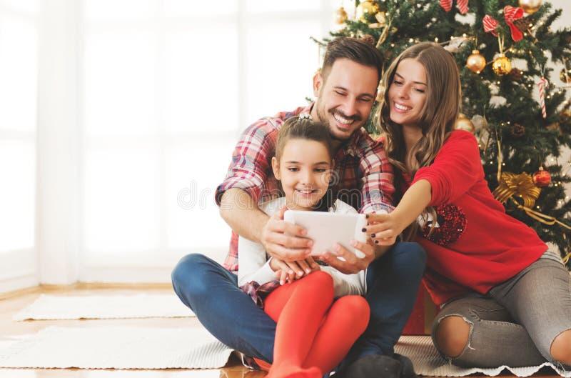 Η οικογένεια σύλλεξε γύρω από ένα χριστουγεννιάτικο δέντρο, χρησιμοποιώντας μια ταμπλέτα στοκ εικόνες