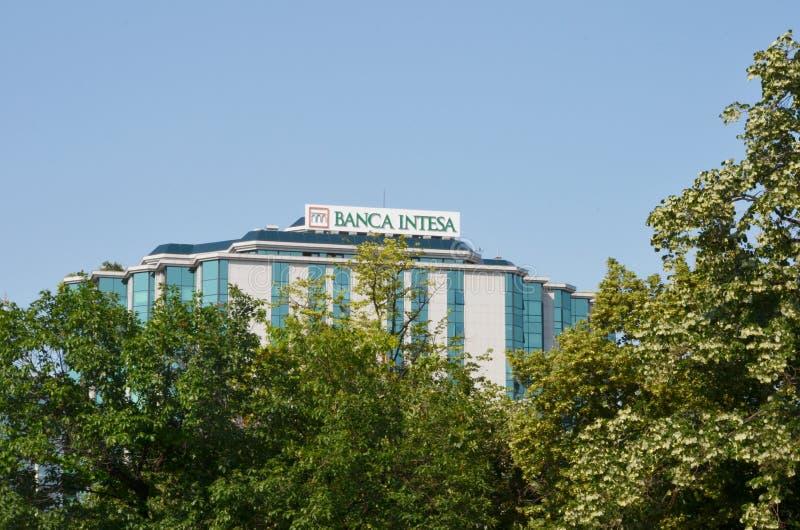 Η οικοδόμηση της τράπεζας Intesa με τον ουρανό ως υπόβαθρο και της πρασινάδας μπροστά από την τράπεζα μέσα στοκ φωτογραφία