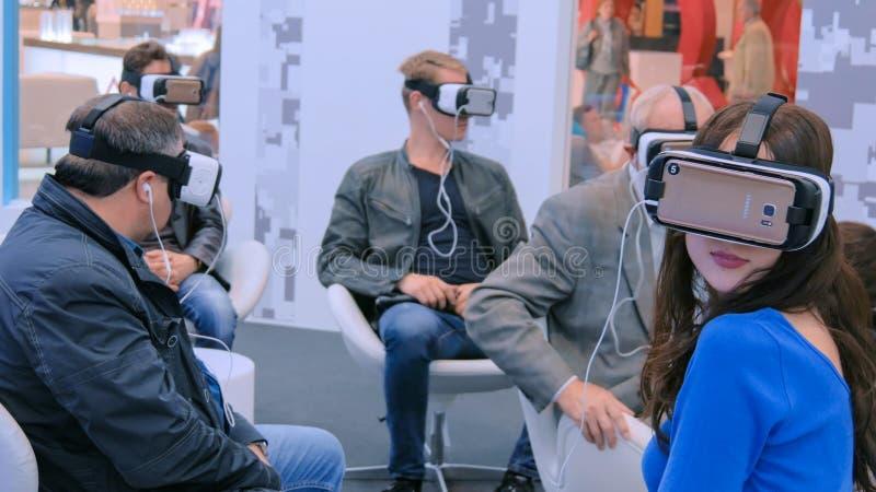 Η ομάδα ανθρώπων που χρησιμοποιεί την κάσκα εικονικής πραγματικότητας στην τεχνολογία παρουσιάζει στοκ φωτογραφία