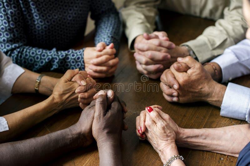 Η ομάδα διαφορετικών χεριών προσεύχεται από κοινού στοκ εικόνες
