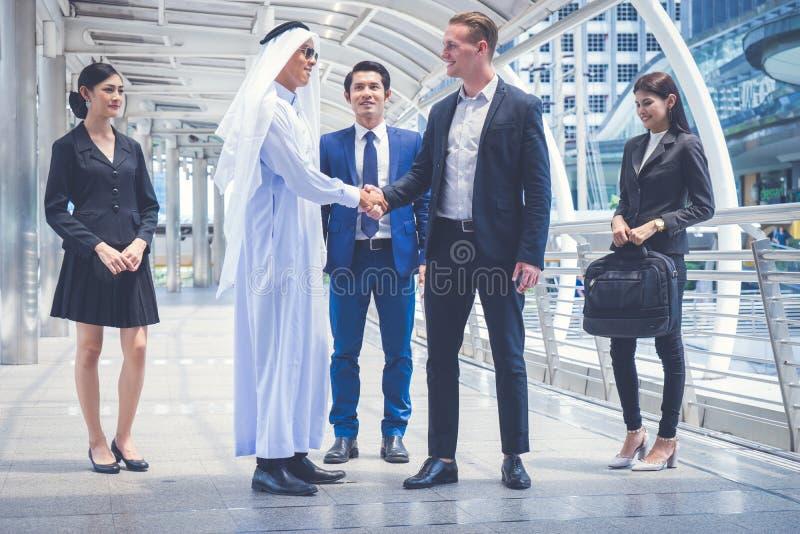 Η ομάδα επιχειρηματιών που στέκονται και που παραδίδει την πόλη για την επιτυχία στις επιχειρησιακές συναλλαγές πολυ πολιτισμός τ στοκ εικόνα