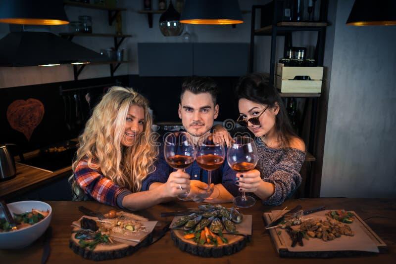 Η ομάδα ευτυχών ανθρώπων που φαίνονται κεκλεισμένων των θυρών και κρατά τα ποτήρια του κρασιού στοκ εικόνα με δικαίωμα ελεύθερης χρήσης