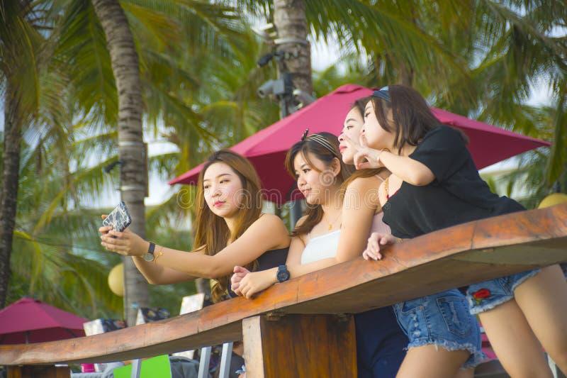 Η ομάδα με τις νέες ευτυχείς και ελκυστικές ασιατικές κινεζικές και κορεατικές γυναίκες που κρεμούν έξω, φίλες που απολαμβάνουν τ στοκ φωτογραφία