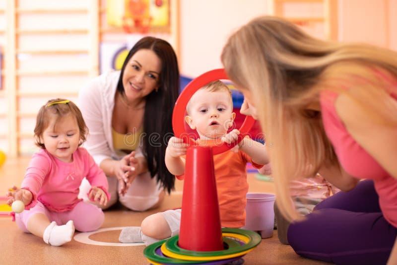 Η ομάδα μωρών βρεφικών σταθμών έχει μια διασκέδαση στη γυμναστική παιδικών σταθμών στοκ εικόνες με δικαίωμα ελεύθερης χρήσης