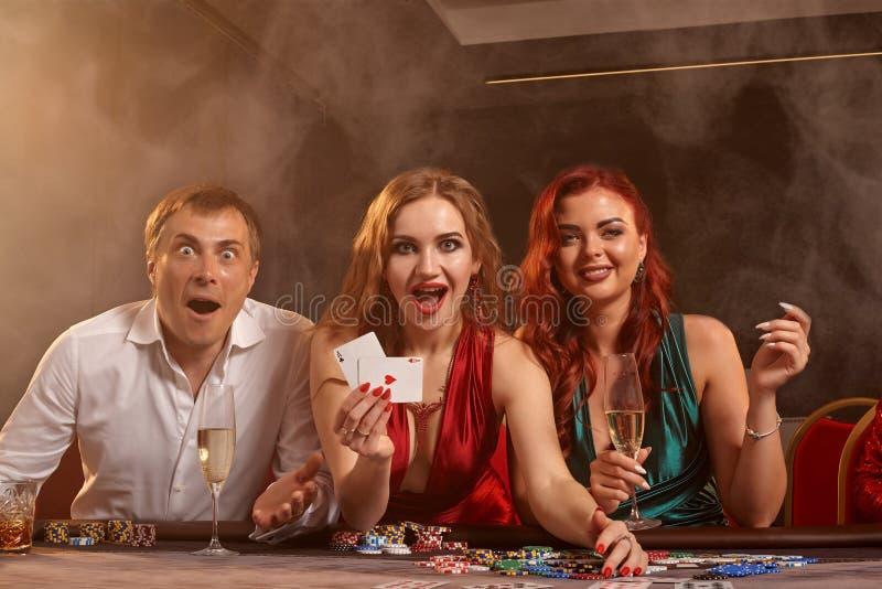Η ομάδα νέοι πλούσιοι φίλοι παίζει το πόκερ σε μια χαρτοπαικτική λέσχη στοκ φωτογραφίες με δικαίωμα ελεύθερης χρήσης