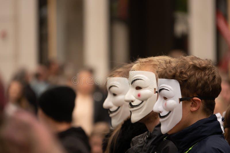 Η ομάδα νέων έντυσε όλων στο Μαύρο βγαίνει στην οδό για να καταδείξει με τις ανώνυμες μάσκες στοκ φωτογραφίες