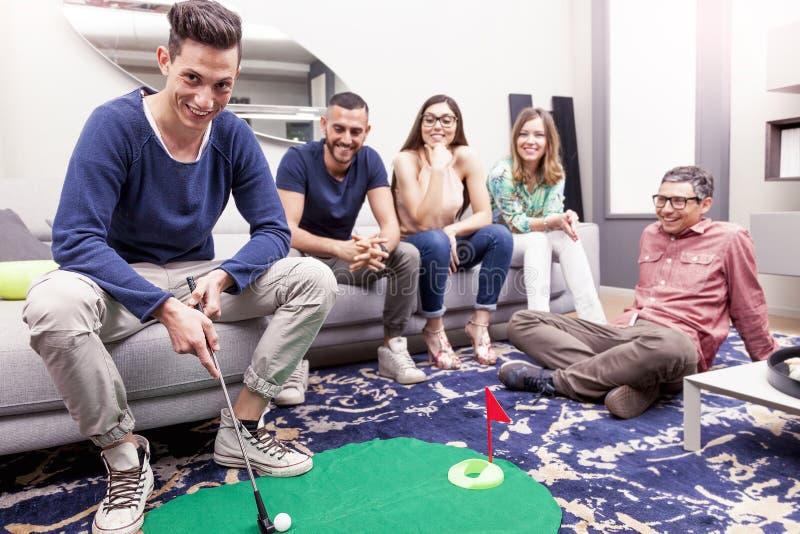 Η ομάδα νέων ενηλίκων έχει το παίζοντας γκολφ διασκέδασης στο καθιστικό στοκ φωτογραφία με δικαίωμα ελεύθερης χρήσης