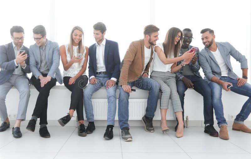 Η ομάδα νέων επικοινωνεί στη αίθουσα αναμονής στοκ εικόνα