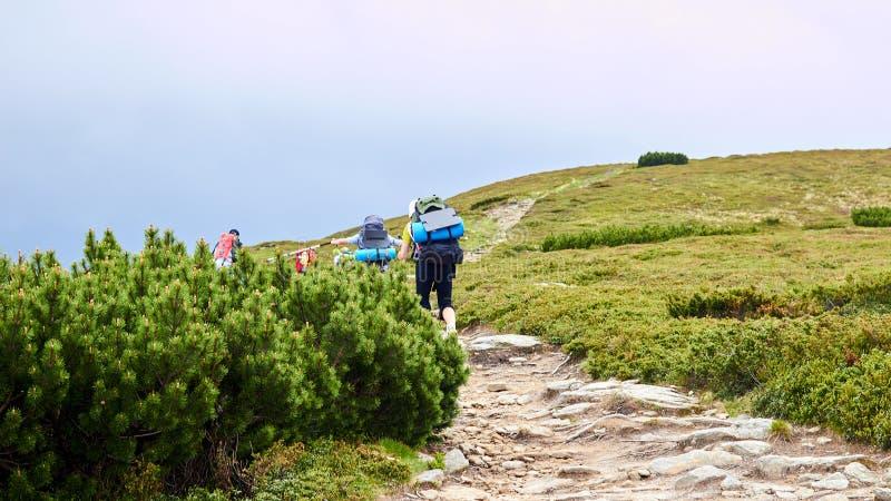 Η ομάδα οδοιπόρων που περπατούν στα βουνά στοκ φωτογραφία