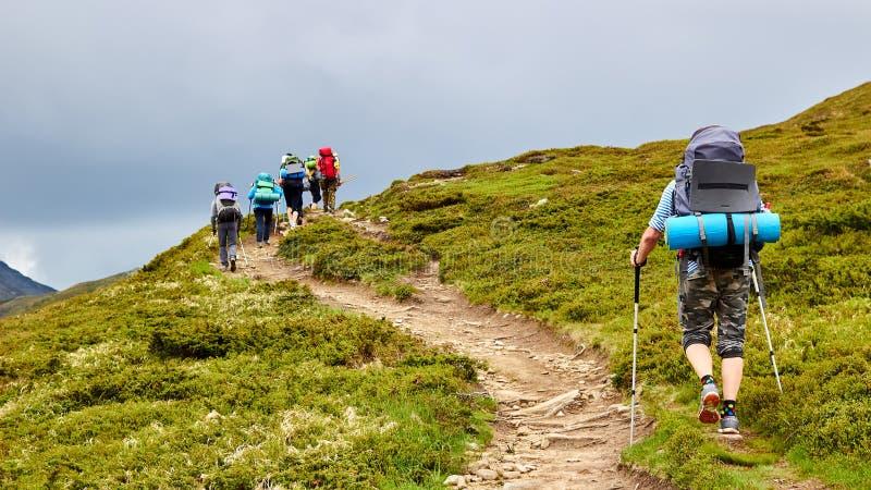 Η ομάδα οδοιπόρων που περπατούν στα βουνά στοκ εικόνες